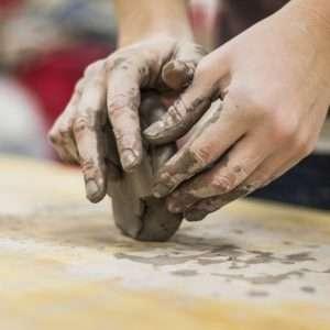 mani che impastano argilla